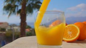Close-upjus d'orange in een glas wordt gegoten dat stock footage