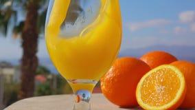 Close-upjus d'orange in een wijnglas wordt gegoten dat stock videobeelden