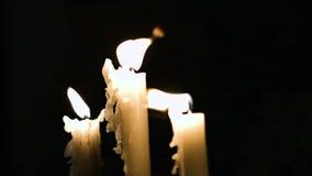 Close-uplengte van drie witte lange en in brand gestoken kaarsen die in weinig pogingen worden geblazen stock footage