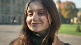 Close-uplengte van schitterend Kaukasisch wijfje dat met grote bruine ogen ontspannen camera bekijkt, cal, ly status stock videobeelden