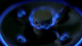 Close-upmacro van de blauwe vlammen van de brander van een gasfornuis wordt geschoten dat Langzaam het aanpassen brandniveau op e stock videobeelden