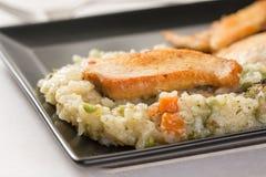Close-upmacro van gebraden kippen wit vlees met risotto in de zwarte vierkante plaat Royalty-vrije Stock Fotografie