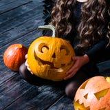 Close-upmeisje die de Halloween-lantaarn van de pompoen hoofdhefboom houden Royalty-vrije Stock Afbeelding