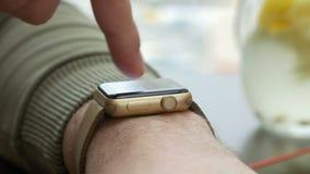 Close-upmening die van de mens aanrakingsgebaren op een wearable slim apparaat van de horlogecomputer maken stock video