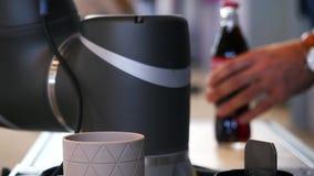 Close-upmening die van robothand de coca-colafles nemen bij de tentoonstelling van het roboticaforum media Robots en innovatief stock footage