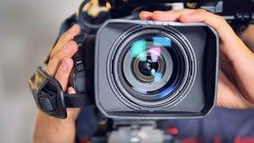Close-upmening over een videocamera door mannelijke handen wordt bewogen die stock videobeelden