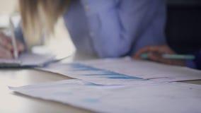 Close-upmening over handen die van werknemers, statistieken binnen analyseren stock videobeelden