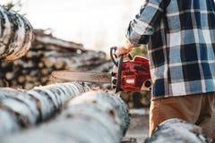 Close-upmening over Professionele sterke houthakker die het gebruikskettingzaag van het plaidoverhemd op zaagmolen dragen stock afbeeldingen