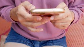 Close-upmening van Aziatische vrouwenzitting op mat en thuis het gebruiken van smartphone stock video