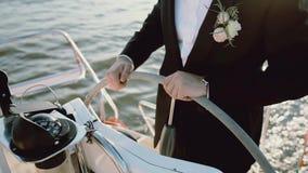 Close-upmening van de bruidegom in een huwelijkskostuum die zich achter stuurwiel op het jacht bevinden Mens die het schip in ove stock video