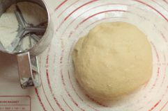 Close-upmening van de eigengemaakte ruwe bal die van het tarwedeeg op de moderne het koken oppervlakte liggen Deeg voor pizza, de Stock Fotografie