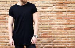 Close-upmening van de gebaarde spiermens zwarte t-shirt dragen en jeans die buiten stellen Lege bruine grungebakstenen muur op stock foto's