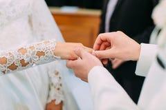 Close-upmening van de hand van de bruidegom die de trouwring op de vinger van de bruid zetten Stock Afbeeldingen