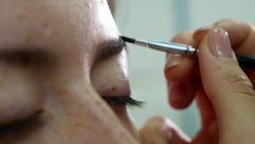 Close-upmening van de handen die van de make-upkunstenaar ` s borstel gebruiken aan verfwenkbrauwen voor een model met valse zwep stock footage