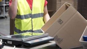 Close-upmening van de handen van een verwerkende arbeider die ingepakte producten in kartondozen zetten, vóór de uitvoer of stock afbeeldingen