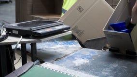 Close-upmening van de handen van een verwerkende arbeider die ingepakte producten in kartondozen zetten, vóór de uitvoer of royalty-vrije stock fotografie