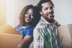 Close-upmening van de Jonge zwarte Afrikaanse mens en zijn meisje bewegende dozen in nieuw huis samen en makend mooi Stock Afbeeldingen