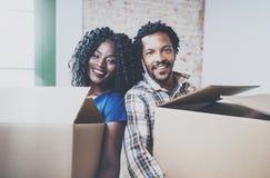 Close-upmening van de jonge zwarte Afrikaanse mens en zijn meisje bewegende dozen in nieuw huis samen en makend succesvol Stock Foto's