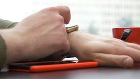 Close-upmening van de mens die een rode smartphone hebben gebruikend een slim horloge in een coffeshop stock videobeelden