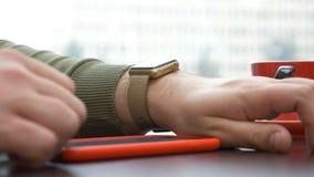 Close-upmening van de mens die een synchronisatie app op smartphone gebruiken en smartwatch stock video