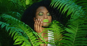Close-upmening van de mooie Afro-Amerikaanse vrouw met groene lippenstift en oogschaduwwen die de wang van zich binnen strijken stock footage
