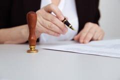 Close-upmening van de vrouwelijke pen van de handholding Document en zegel op het bureau royalty-vrije stock afbeelding
