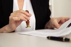 Close-upmening van de vrouwelijke zegel van de handholding en notarieel bekrachtigd document royalty-vrije stock afbeelding