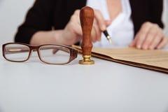 Close-upmening van de vrouwelijke zegel van de handholding en notarieel bekrachtigd document Glassess dichtbij royalty-vrije stock foto's