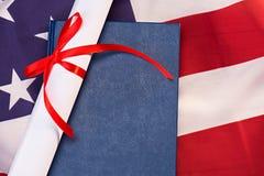 Close-upmening van diploma en boek op Amerikaanse vlag royalty-vrije stock foto's