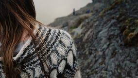 Close-upmening van donkerbruin vrouwelijk haar die op de wind golven Jonge vrouw die in lopapeysasweater in de bergen wandelen stock footage