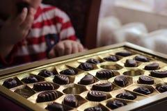 Close-upmening van doos chocolade Kind dat suikergoed eet hebzucht royalty-vrije stock foto