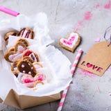 Close-upmening van doos met zoete gastronomische valentijnskaartenkoekjes met liefdeetiket Stock Foto