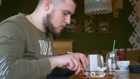 Close-upmening van een jonge mens die met smartwatch heerlijke cake in een koffie eten stock video