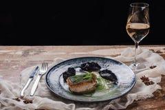 close-upmening van gebraden gastronomisch zander en glas wijn stock foto