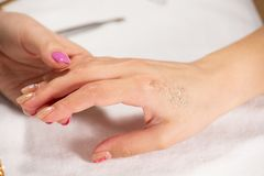 Close-upmening van handen met manicure van de jonge behandeling van de vrouwenspijker door een specialist in de salon royalty-vrije stock afbeelding
