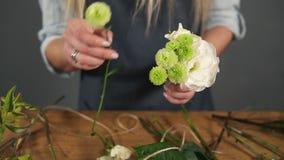 Close-upmening van handen van professionele blonde vrouwelijke bloemenkunstenaar die mooi boeket schikken bij bloemwinkel florist stock video