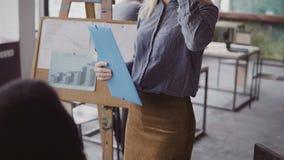 Close-upmening van het vrouwelijke manager lopen door het bureau met documenten Multiraciale teamklap aan onderneemster stock afbeelding