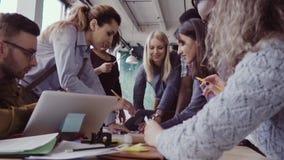 Close-upmening van jong commercieel team die dichtbij de lijst, brainstorming samenwerken Vrouwelijke teamleider die ideeën bespr stock videobeelden