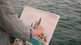 Close-upmening van jong creatief paar die hobby op de kust van overzees doen Vrouwentekening, man het spelen gitaar stock video