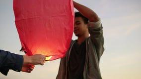 Close-upmening van jong multi-etnisch paar die rode document lantaarn houden alvorens te lanceren Aantrekkelijke vrouw met haar A stock footage