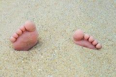 Close-upmening van kleine die voeten met tenen in het zand door het zonsonderganglicht wordt aangestoken Stock Afbeelding