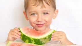 Close-upmening van leuk weinig jongenszitting bij de lijst aangaande de keuken Mannetje die een stuk houden en een watermeloen et stock videobeelden