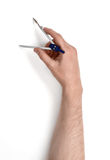 Close-upmening van man& x27; s hand met tekeningskompas, op witte achtergrond wordt geïsoleerd die Stock Afbeelding