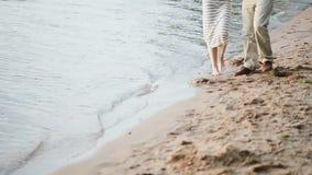 Close-upmening van mannelijke en vrouwelijke voeten die op het strand dichtbij het water lopen Jonge paar het besteden tijd op de stock footage