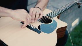 Close-upmening van mannelijke handen die de gitaar houden en reparatie maken Musicusmens die het koord op instrument veranderen stock videobeelden