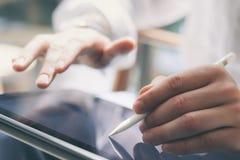 Close-upmening van mannelijke handen die digitale tablet op hand houden en elektronische pen gebruiken terwijl het werken op zonn Stock Afbeelding