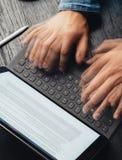 Close-upmening van mannelijke handen die snel op elektronische tablet toetsenbord-dok post typen tekstinformatie over het apparat royalty-vrije stock afbeelding