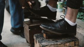 Close-upmening van mannelijke voeten op een tribune Schoenshiner die aan de straat werken, die de zwarte schoenen binnen de stad  stock footage