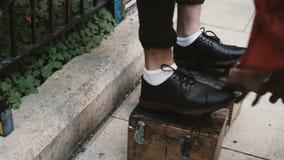 Close-upmening van mannetje, zakenmanvoeten op een tribune Schoenshiner die aan de straat werken, die de zwarte schoenen oppoetse stock videobeelden