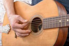 Close-upmening van mensen` s hand het spelen gitaar Stock Fotografie